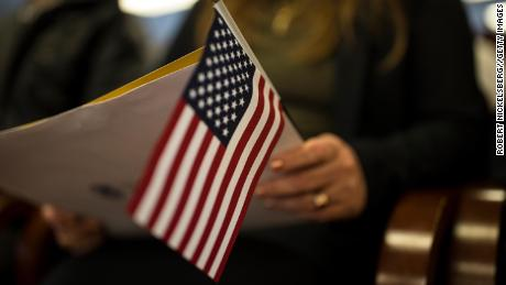 A newly sworn in US citizen holds a US flag while listening to a speech from a US government employee at a naturalization ceremony for new US citizens in February 2017 in Newark, New Jersey.