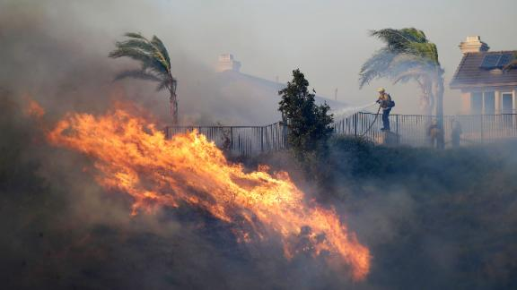 A firefighter sprays water in front of an advancing wildfire Friday, Oct. 11, 2019, in Porter Ranch, Calif.
