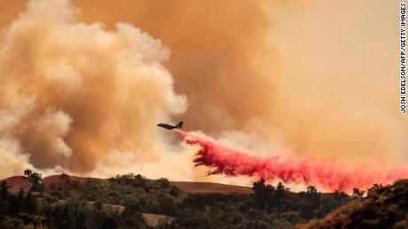 An aircraft helps fight the Saddleridge fire by dropping fire retardant along a ridge in Newhall, California on October 11, 2019. - Much of California was on high alert Friday as wind-driven wildfires tore through the state's south, forcing the evacuation of tens of thousands of people and destroying multiple structures and homes. Fire officials said an 89-year-old woman died in Calimesa, about 70 miles (115 kilometers) east of Los Angeles, when a fire swept through a trailer park overnight after the driver of a garbage truck that caught fire dumped his burning load nearby.
