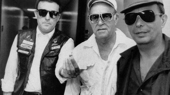 Giuliani, left, holds two vials of crack cocaine he bought while working undercover in July 1986. With him are US Sen. Alphonse D'Amato, right, and Benjamin Bear, chairman of the U.S. Parole Commission.