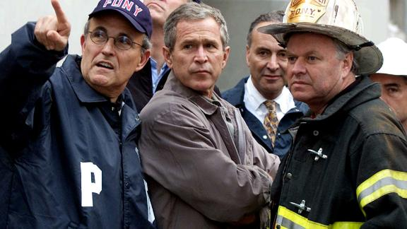 Giuliani, left, accompanies US President George W. Bush and other officials during a tour of the fallen World Trade Center in September 2001.