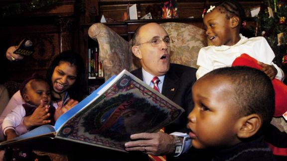"""Giuliani reads """"The Night Before Christmas"""" to children while visiting an orphanage in New York in December 2004."""