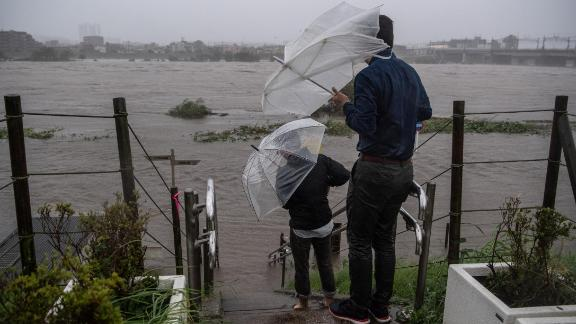 People look at the flooded Tama River in Tokyo on October 12.