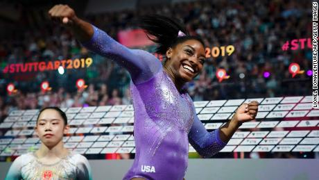 USA's Simone Biles (R) celebrates after winning the beam apparatus final as second placed China's Liu Tingting looks on at the FIG Artistic Gymnastics World Championships at the Hanns-Martin-Schleyer-Halle in Stuttgart, southern Germany, on October 13, 2019.