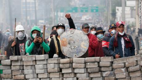Anti-government demonstrators man a barricade during clashes with the police.