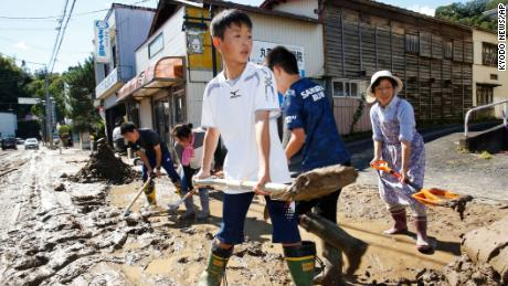 Students and residents scoop dirt as the town is flooded Typhoon Hagibis, in Marumori, Miyagi prefecture, northern Japan, Sunday, Oct. 13, 2019. Rescue efforts for people stranded in flooded areas are in full force after a powerful typhoon dashed heavy rainfall and winds through a widespread area of Japan, including Tokyo.