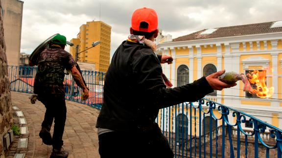 Demonstrators throw a Molotov cocktail during of protests in Quito on Saturday.