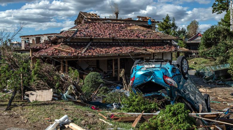 An upturned car lies next to a partially destroyed house after being hit by a tornado shortly before the arrival of Typhoon Hagibis, on October 13, 2019 in Chiba, Japan.