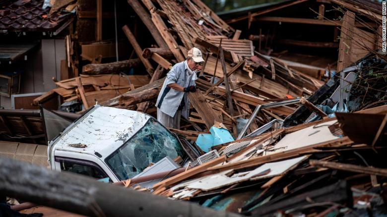A man sorts through the debris of a building that was destroyed by a tornado shortly before the arrival of Typhoon Hagibis, on October 13, 2019 in Chiba, Japan.