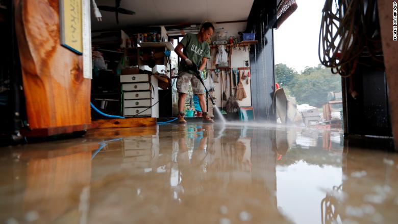 A volunteer helps clean up Monday, October 14, 2019, in Kawagoe City, Japan.
