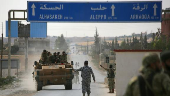 Turkish-backed Syrian fighters are pictured in the town of Ayn al-Arus, south of the border town of Tal Abyad, on October 14, 2019, as Turkey and it's allies continues their assault on Kurdish-held border towns in northeastern Syria. - Syrian regime forces moved towards the Turkish border after Damascus reached a deal with beleaguered Kurdish forces following a US withdrawal announcement, AFP correspondents reported. (Photo by Bakr ALKASEM / AFP) (Photo by BAKR ALKASEM/AFP via Getty Images)