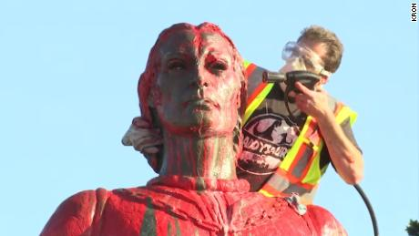 A worker sprays red paint off of a statue of Christopher Columbus on Sunday in San Francisco.
