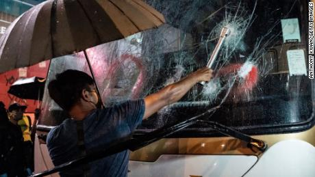 HONG KONG, CHINA - OCTOBER 13: A pro-democracy protester attempts to break a tourist bus front windows in Mongkok district on October 13, 2019 in Hong Kong, China. Hong Kong's government invoked emergency powers last week to introduce an anti-mask law which bans people from wearing masks at public assemblies as the city remains on edge with the anti-government movement entering its fourth month. Protesters in Hong Kong continue to call for Chief Executive Carrie Lam to meet their remaining demands since the controversial extradition bill was withdrawn, which includes an independent inquiry into police brutality, the retraction of the word riot to describe the rallies, and genuine universal suffrage, as the territory faces a leadership crisis.