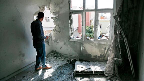 A person inspects damage to a building in Akcakale, Turkey, on Sunday, October 13. The building was damaged by a mortar fired from inside Syria.