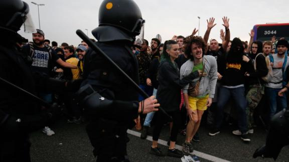 Protesters clash with Spanish policemen on the highway leading to El Prat airport in Barcelona on October 14, 2019 as thousands of angry protesters took to the streets after Spain