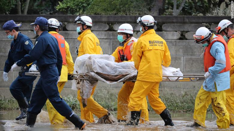 Police officers and fire fighters carry a dead body on a street after the flood in Koriyama City, Fukushima Prefecture Monday, October 14.
