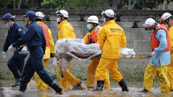 Police officers and fire fighters carry a dead body on a street after the flood in Koriyama City, Fukushima Prefecture on Monday.