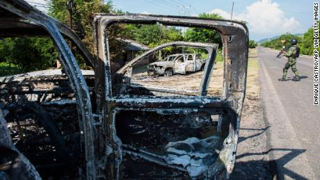 Picture of police vehicles torched by gunmen who also killed 14 police officers in an ambush in the community of Aguililla, in the Mexican state of Michoacan, on October 14, 2019. - Local media reports said the state police were executing a warrant on the outskirts of Aguililla, in the restive region in western Mexico, a hotspot for criminal groups and vigilantes, when gunmen in armoured four-by-four trucks opened fire. They torched at least two patrol cars in the ensuing chaos and left signs with threatening messages directed at the security forces at the scene. (Photo by Enrique CASTRO / AFP) (Photo by ENRIQUE CASTRO/AFP via Getty Images)