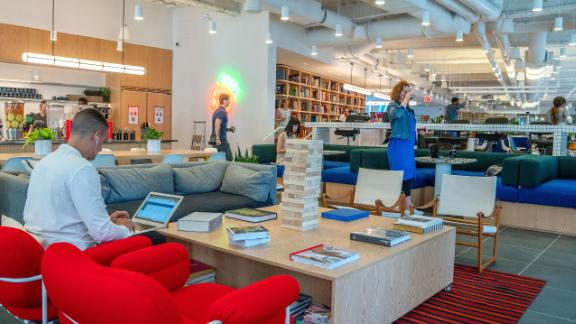 Members work in a cafeteria and lounge area at the WeWork Cos Inc. 85 Broad Street offices in the Manhattan borough of New York, U.S., on Wednesday, May 22, 2019. WeWork has become the biggest private office tenant in London, Manhattan and Washington on its way to 425 office locations in 36 countries overall.