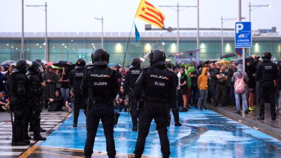 Police watch as protesters block access to Barcelona Airport on October 14.