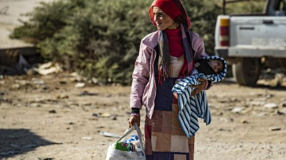 A Syrian woman fleeing the battle zone between Turkey-led forces and Kurdish fighters from the Syrian Democratic Forces on the border with Turkey.