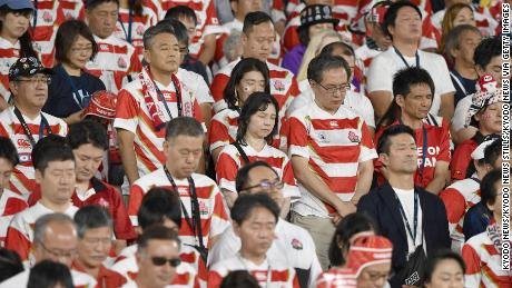 Spectators observe a moment of silence ahead the match between Japan and Scotland in memory of the victims of Typhoon Hagibis that ripped through wide areas of Japan the previous day.