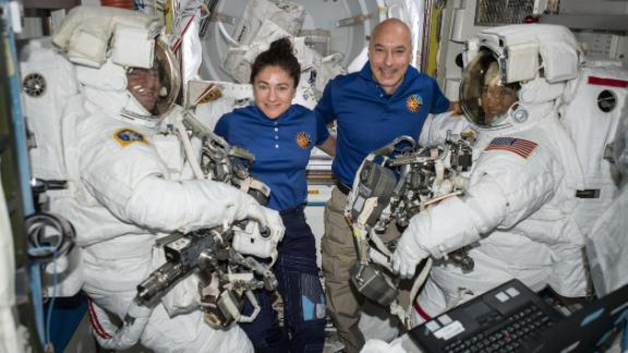 NASA astronauts Andrew Morgan (left) and Christina Koch (right) are suited up in US spacesuits, assisted by NASA Flight Engineer Jessica Meir and European Space Agency Commander Luca Parmitano.