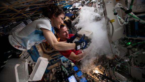 NASA astronauts Christina Koch and Andrew Morgan store research samples in a science freezer inside the U.S. Destiny laboratory module.