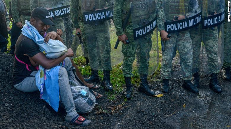 A migrant tends to a child while surrounded by members of the National Guard near Tuzantan, Mexico, on October 12.