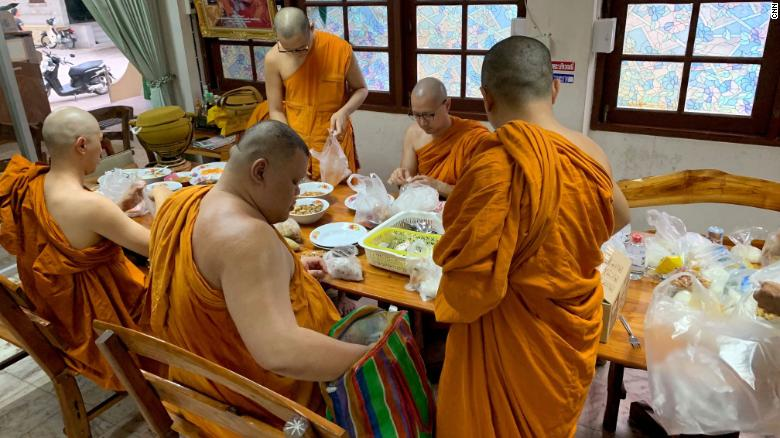 Monks at Yannawa temple in Bangkok prepare to eat.