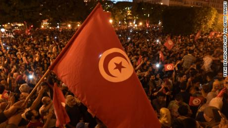 Tunisians gather to celebrate the victory of Kais Saied in the Tunisia's presidential runoff on October 13, 2019, in the capital Tunis. - Conservative academic Kais Saied, a political outsider, won a landslide victory Sunday in Tunisia's presidential runoff, sweeping aside his rival, media magnate Nabil Karoui, state television said. (Photo by Fethi Belaid / AFP) (Photo by FETHI BELAID/AFP via Getty Images)