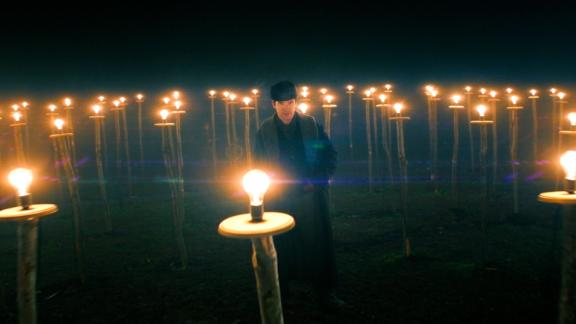"""Benedict Cumberbatch's Thomas Edison illuminates a barren field in Menlo Park, New Jersey with incandescent light bulbs from the film """"The Current War."""""""
