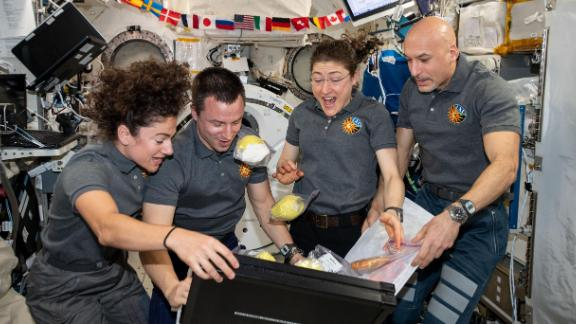 Four Expedition 61 crewmembers unpack fruit and other space-friendly food from a storage bag.