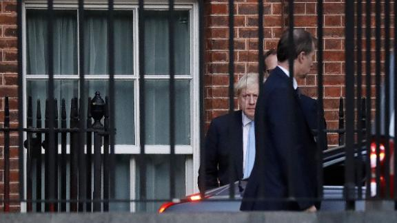 "Britain's Prime Minister Boris Johnson (L) leaves from the rear of 10 Downing Street in central London on October 16, 2019. - British Prime Minister Boris Johnson briefed his ministers and key lawmakers on Wednesday on details of a Brexit deal taking shape in Brussels, while warning an agreement was still ""shrouded in mist"". (Photo by Tolga AKMEN / AFP) (Photo by TOLGA AKMEN/AFP via Getty Images)"