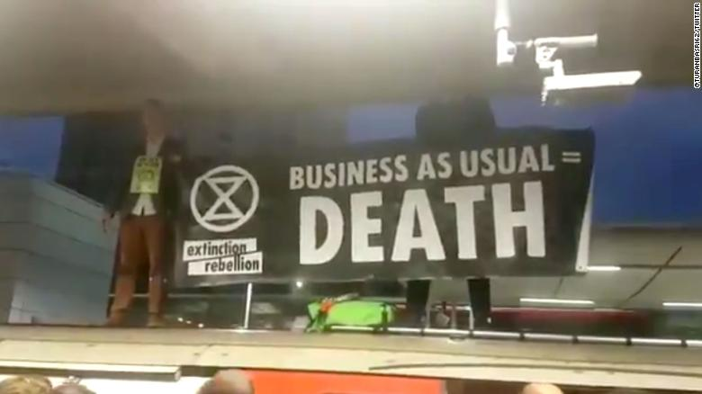 "Extinction Rebellion protesters hold a sign that reads: ""Business as usual = Death."""