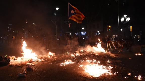 A Catalan flag flies above burning rubbish in Barcelona on October 15.