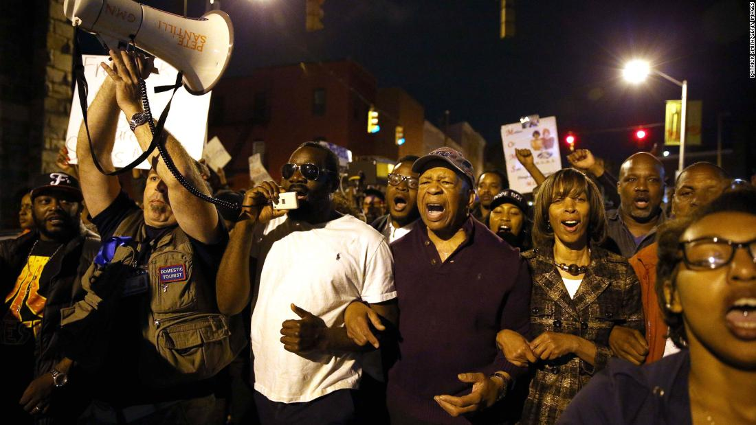 Cummings marches with protesters in Baltimore after authorities released a report on the death of Freddie Gray.