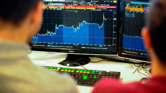 Journalists pose looking at a computer screen with the Bloomberg display showing a three-day view showing the rise and fall in the value of the pound sterling against the US dollar in London on October 17, 2019 with a spike (R) at the moment of the announcement of a draft Brexit deal. - Sterling surged within a whisker of $1.3 on October 17, 2019, striking five-month peaks as the European Union reached a draft Brexit withdrawal deal with London. (Photo by DANIEL SORABJI / AFP) (Photo by Daniel Sorabji/AFP via Getty Images)