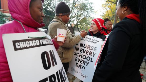 Striking teachers and support staff picket outside the John J. Pershing Magnet School on the first day of their strike in the city's Bronzeville neighborhood Thursday, Oct. 17, 2019, in Chicago. Chicago teachers went on strike Thursday, marching on picket lines after failing to reach a contract deal with the nation's third-largest school district in a dispute that canceled classes for more than 300,000 students. (AP Photo/Charles Rex Arbogast)