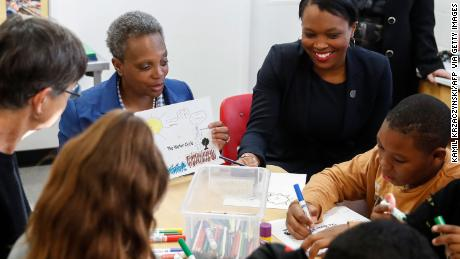 Mayor Lori Lightfoot, second from left, and CEO of Chicago Public Schools Janice Jackson, right, looks to students at the McCormick YMCA from Metro Chicago on Thursday.