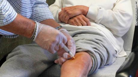 A doctor injects cortisone into a patient's knee.