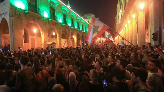 Demonstrators wave flags outside the government palace in Beirut on October 17.
