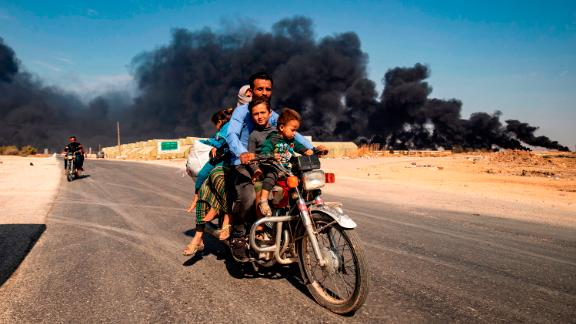 Displaced people ride a motorcycle on the outskirts of Tal Tamr, Syria, on Wednesday, October 16.