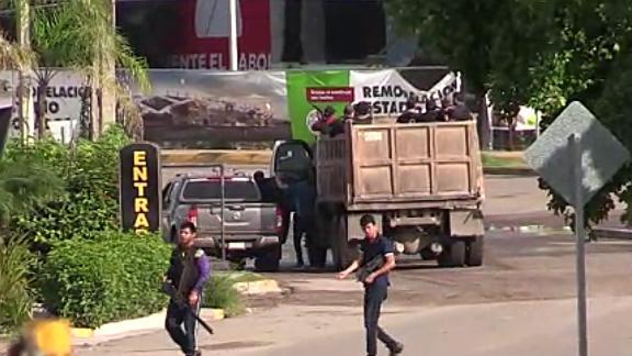 Gunmen are seen in a Culiacan street Thursday.