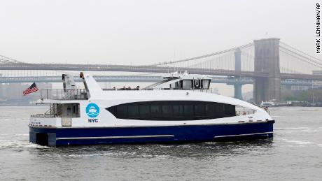 A New York City Ferry passes the Brooklyn Bridge.