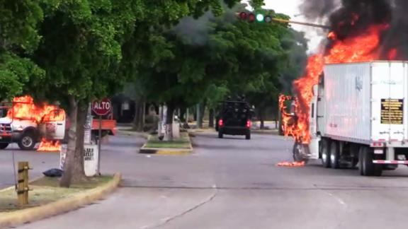 """In this AFPTV screen trucks burn in a street of Culiacan, state of Sinaloa, Mexico, on October 17, 2019. - Heavily armed gunmen in four-by-four trucks fought an intense battle against Mexican security forces Thursday in the city of Culiacan, capital of jailed kingpin Joaquin """"El Chapo"""" Guzman"""