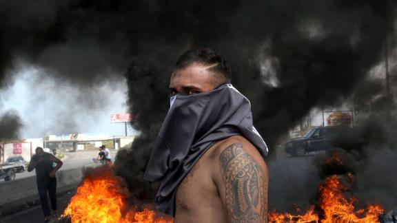 A Lebanese demonstrator stands in front of a tire fire on Friday.