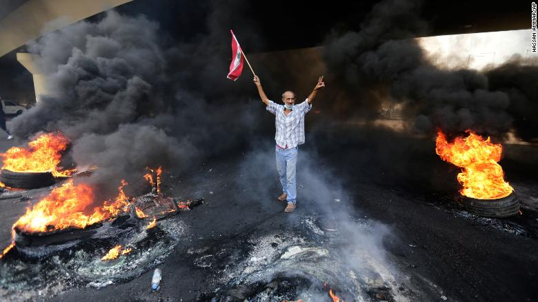 An anti-government protester makes a victory sign, while holding a Lebanese flag and walking past blazing tires during a protest on October 18.