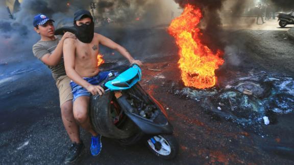 Lebanese demonstrators drive past burning tires during a demonstration on Thursday.