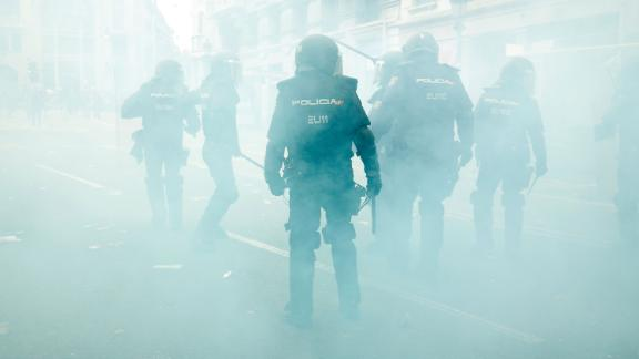 Spanish national police officers stand in the smoke as they protect the police headquarters in Barcelona.